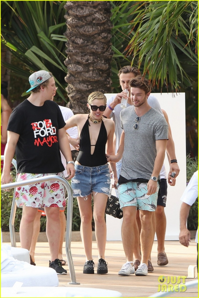Miley Cyrus and her boyfriend Patrick Schwarzenegger hang out with friends, including Cody Simpson, poolside in Miami