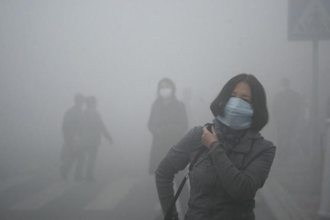 Девушка идет по Пекину, который весь в смоге. Уровень загрязнения превышает норму в 40 раз.