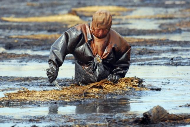 Рабочий снимает нефтяную пленку с воды