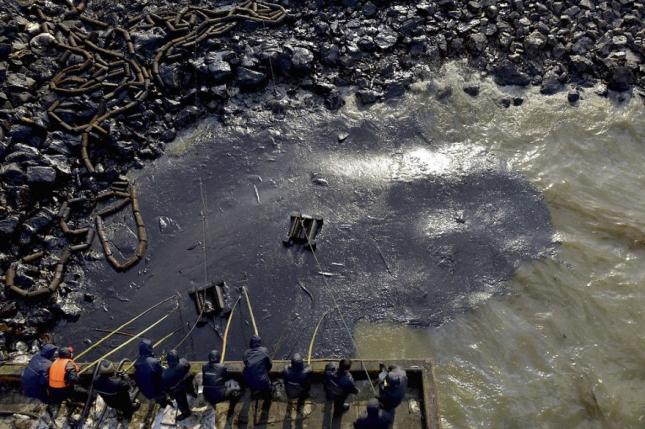 Разлитый отходы нефтепереработки вычерпывают ведрами