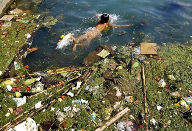 Ребенок купается в грязном водохранилище в Пингбоу