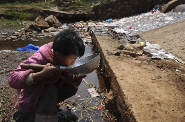 ребенок пьет воду в городе Фуюань в провинции Юньнань.