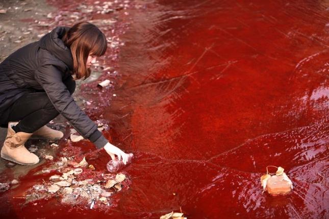 журналист зачерпывает грязную воду в реке  Цзянхе