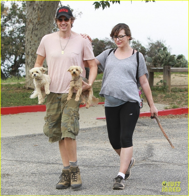 Milla Jovovich tries to conceal her baby bump for a hike with Paul