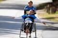 Папа с сыном принимает участие в спортивных марафонах на сделанной для двоих специальной инвалидной коляске.