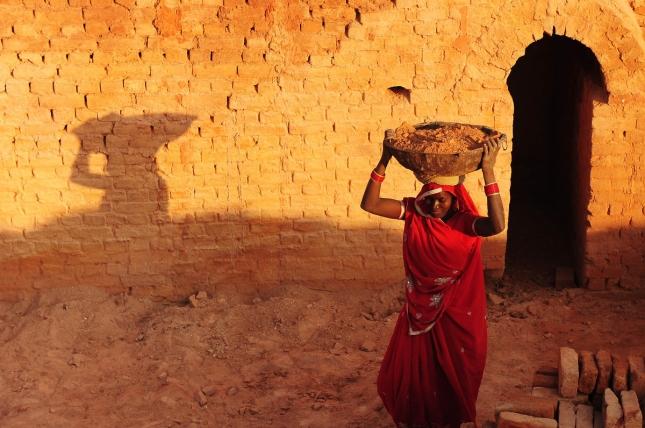 Аллахабд, Индия. Женщина-разнорабочая носит кирпичи.