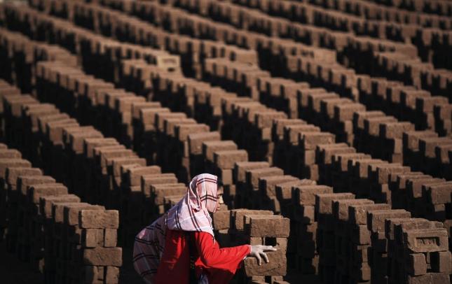 Кирпичный завод в Пакистане. Исламбад. женщина складывает кирпичи на просушку. Работа идет от заката до рассвета, а платят тут сущие гроши - едва хватает прокормить семью и маленьких детей.