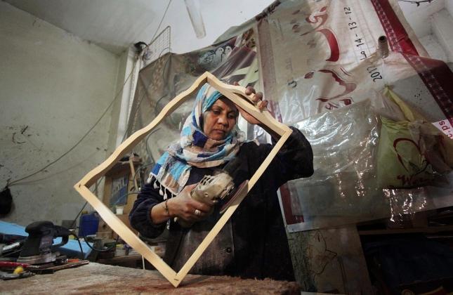 Палестинка работает - изготавливает рамы в мастерской, в Секторе Газа