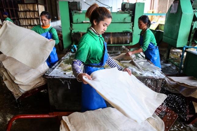 Район, Таиланд. Девушки создают изделия на резиновой фабрике.