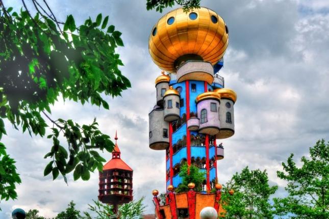 Башня Хундертвассера — воистину сказочный домик. Даже не верится, что такая красота сущетвует в реальности. В высоту смотровая башня Kuchlbauer занимает 35 метров, а находится она рядом с одноименным пивоваренным заводом в Абенсберге. Находится город в Нижней Баварии, в Германии. Когда архитектора не стало, башню достраивал согласно проекту владелец данного пивоваренного завода Леонард Заллек совместно с архитектором Питером Пеликаном.