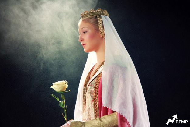 Аврора, «Спящая красавица», Англия, 14 век На самом деле, деталей не так много, но удалось выудить, что фильм начинается с момента, как принцесса пролистывает манускрипт в золотой окантовке узором из листьев, такие как раз начали создавать в примерно это историческое время. Принцесса ассоциируется с символом розы, который получил особое распространение в те годы. Ну и главный акцент, когда принц хочет жениться на простой крестьянке и говорит отцу Губерту, что тот живет в прошлом, а «ведь на дворе 14 век». Крестьянки носили пышные и маскирующие тело одежды, а знатным особам дозволялось надевать облегающие лиф и руки платья. Лиф украшали броши, а спинку платья шикарные шлейфы, особенно прекрасно смотрелись прически: затейливо заплетенные косы и венцы или короны из волос. Блондинки считались особенно привлекательными, а вот брюнеток не жаловали, поэтому, разумеется, красавицей могла считаться только блондинка.