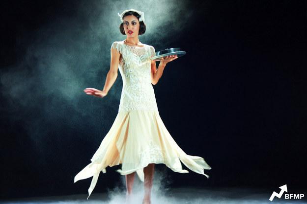 """Тиана, """"Принцесса и лягушка"""", 1920-ые, Новый Орлеан.В начале ленты говорится, что Тиана была лучшей швеей в Новом Орлеане. Джазовые композиции, ниспадающие фалды юбки и автомобили в стиле фильма о великом Гэтсби намекают нам на то, что это были точно 1920-ые. Помимо весьма характерного стиля одежды Тианы можно отметить, что женщины носили короткий боб, а также шикарные головные уборы, которые подчеркивали стрижку. Бровки рисовались явственно, подкрашивались карандашом. В чести была подводка для глаз, пышные слои туши для ресниц, ярко нарумяненные щеки и алая кричащая помада."""