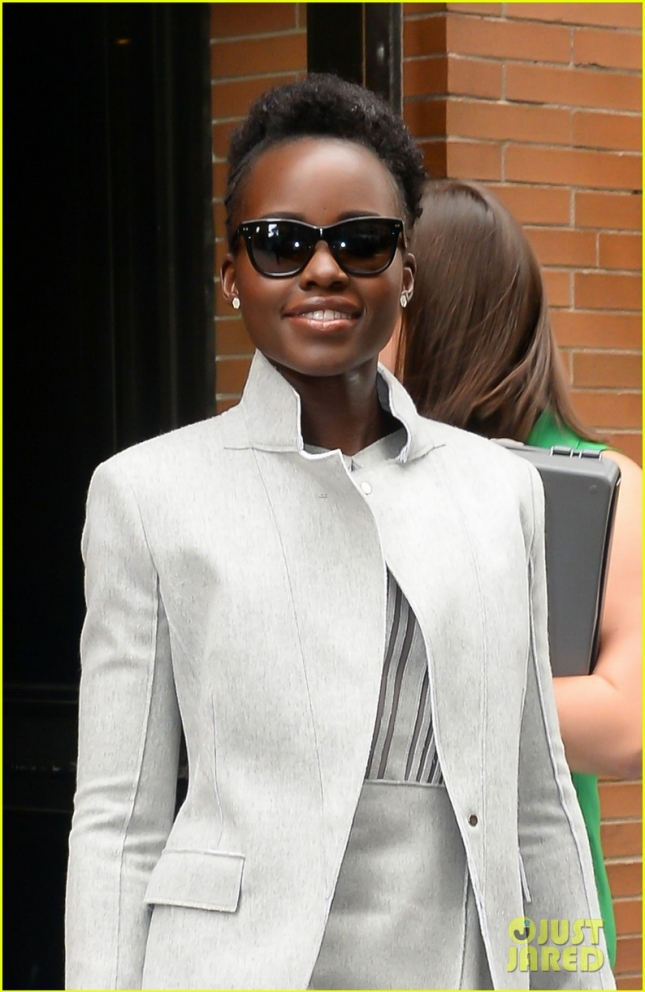 Lupita leaving the View in NYC wearing a grey outfit and a red shoes with her grey pocketbook