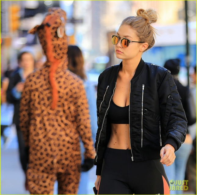 Gigi Hadid is all smiles when walking past a guy in a giraffe costume, showing off her toned stomach and chest in Soho, NY